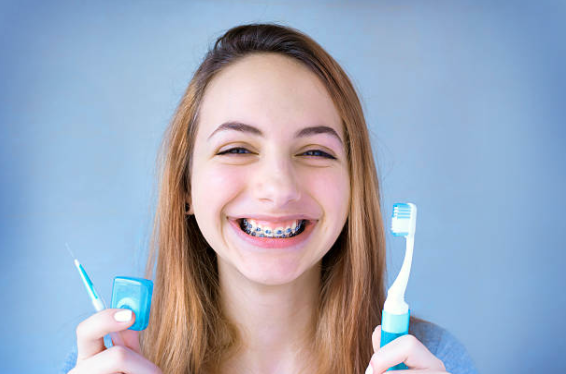 Girl with braces holding toothbrush and floss